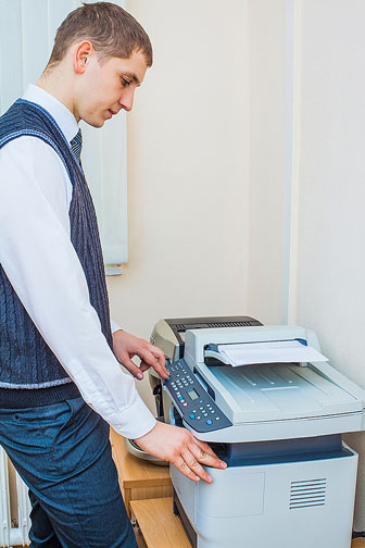 office worker using a multifunction printer to make copies